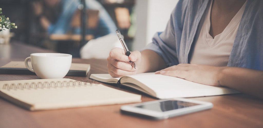 woman sitting in a coffee shop writing