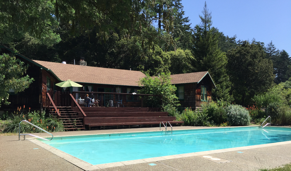 photo of the Pescadero retreat center with the pool in the foreground and forest in the background
