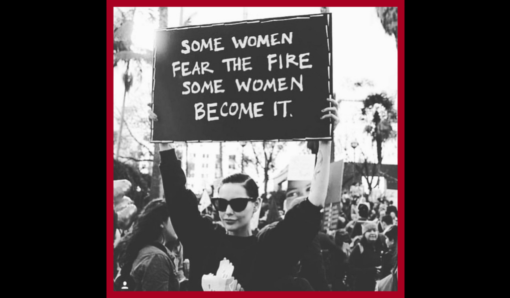 "Black and white photo of a woman holding a protest sign that reads ""Some women fear the fire. Some women become it."""