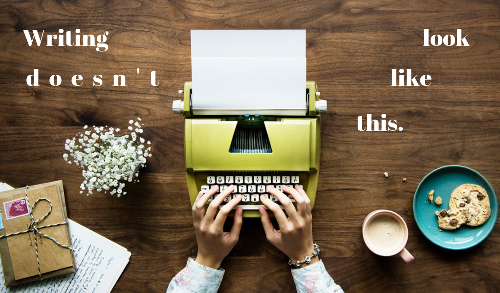"""Overhead photo of a woman's hands typing on a green typewriter. To the left is an open notebook, a stack of letters, and flowers. To the right is a latte and a cookie on a blue plate. The text added to the photo reads """"Writing doesn't look like this."""""""